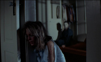 Jamie Lee Curtis as Laurie Strode, shown trotting away from serial killer Michael Meyers in Halloween.