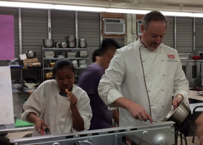"""Executive Chef Ryan Day from Palama Meat Company guides culinary students with preparing watermelon poke, lemongrass chicken, kalua kale soup, shrimp with broccoli leaves, fresh corn, and kabocha and cantaloupe cupcakes. Culinary students visited Aloun Farms on Sept. 10, and returned to school with donated produce from the farm. """"We got to see how the fruits and vegetables get started, and to see the difference between store bought and farm fresh,"""" culinary teacher Jamie Kahalewai said."""