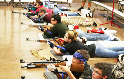 Air riflery members Sam Sharpe (10), Alexander Roynon (9), Kortni Baughman (10), Anthony Hewitt (10), David Pounds (12), Bailey Wells (12), and Alysa Wipperman (11) take on a prone position, where they lay on their stomach shooting 20 targets for 20 minutes during practice in the school cafeteria. Hawaii is one of 18 states this sport is offered to high school students. Photo by Alyssa Green