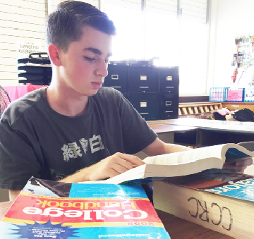 "Matthew Mann (11) peruses through College and Major Handbooks during TASK. Two hundred two students took the PSAT during the fall break. ""I feel the PSAT is the best method of practice to predict how one will do on the actual SAT,"" he said."