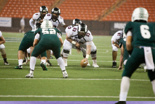 "Wide Receiver and Kick Returner DJ Morton (10) motions pre-snaps while Quarterback Quintin Iriarte (12) takes the snap from Offensive Line Tayvis Passos (12). Rams beat Kapaa Warriors (30-16) to win the State Division II Football Championship title.""It feels great knowing you're a champ forever,"" Defensive Back Sipa Leafa (11) said."