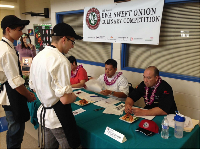"Culinary students Evan Collins (11) and Jeremiah Joswick (11) at the Aloun Farms 3rd Annual Ewa Sweet Onion Culinary Competition. The objective of the competition is to cook a dish with the items assigned to your team. ""It was a good learning experience,"" Joswick said. (Photo submitted by Evan Collins)"