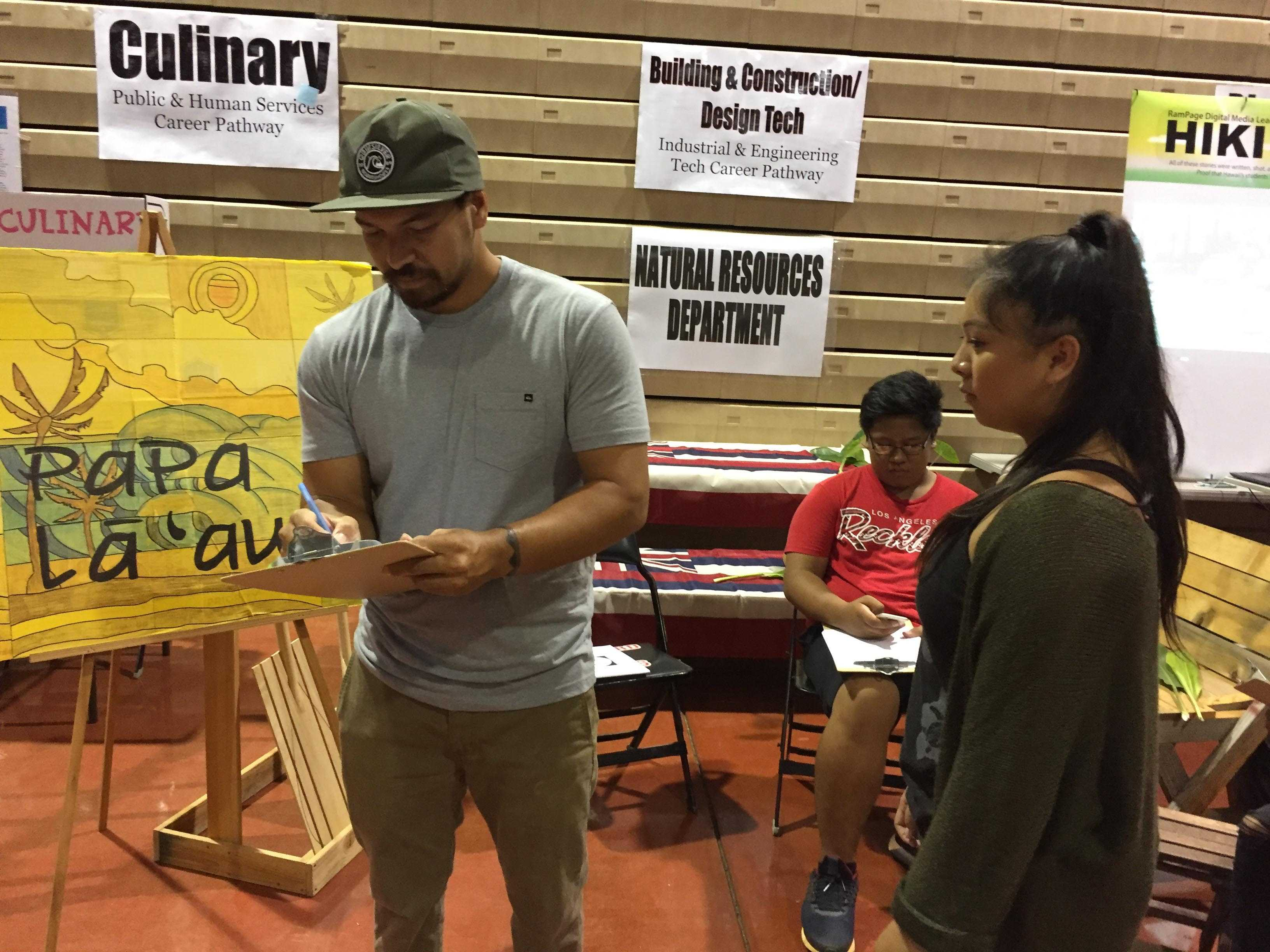 Career Technical Education teacher Kapuni Patcho distributes registration stickers for his Papa La'au course at Project ARIES' Curriculum Fair. Over 20 departments and programs promoted their courses, and addressed students and their parents' questions at the evening fair. The fair is part of a two-week schoolwide event that also features a Career and College Fair for students