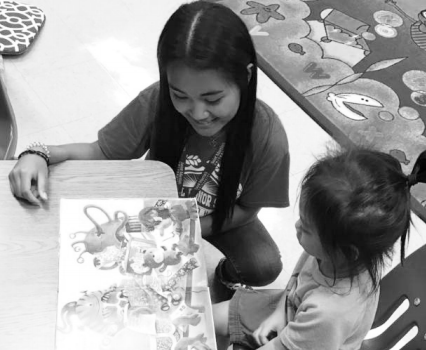 Rashelle Bumanglag (12) reads to a preschooler at Makalapa Elementary. NHS members visited the school multiple times this quarter during TASK and recess to read to students. Photo Submitted by Kristine Namnama